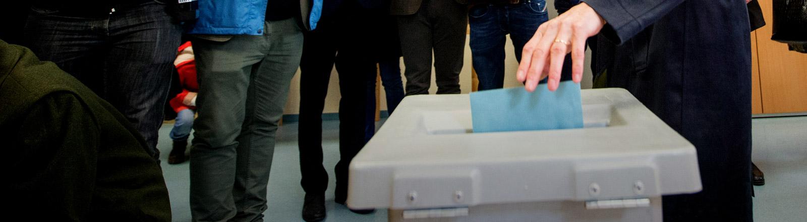 Eine Frau wirft einen Wahlzettel in eine Wahlurne