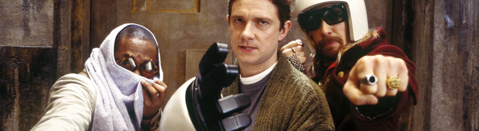 """Mos Def als Ford Prefect, Martin Freeman als Arthur Dent and Sam Rockwell als Zaphod Beeblebrox in der Verfilmung der Science-Fiction-Trilogie """"Per Anhalter durch die Galaxis""""."""