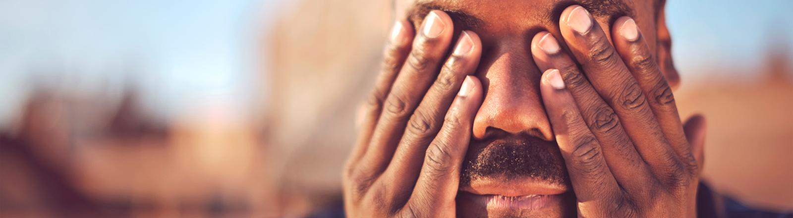 Ein Mann mit dunkler Hautfarbe hält sich die Augen mit den Händen zu.