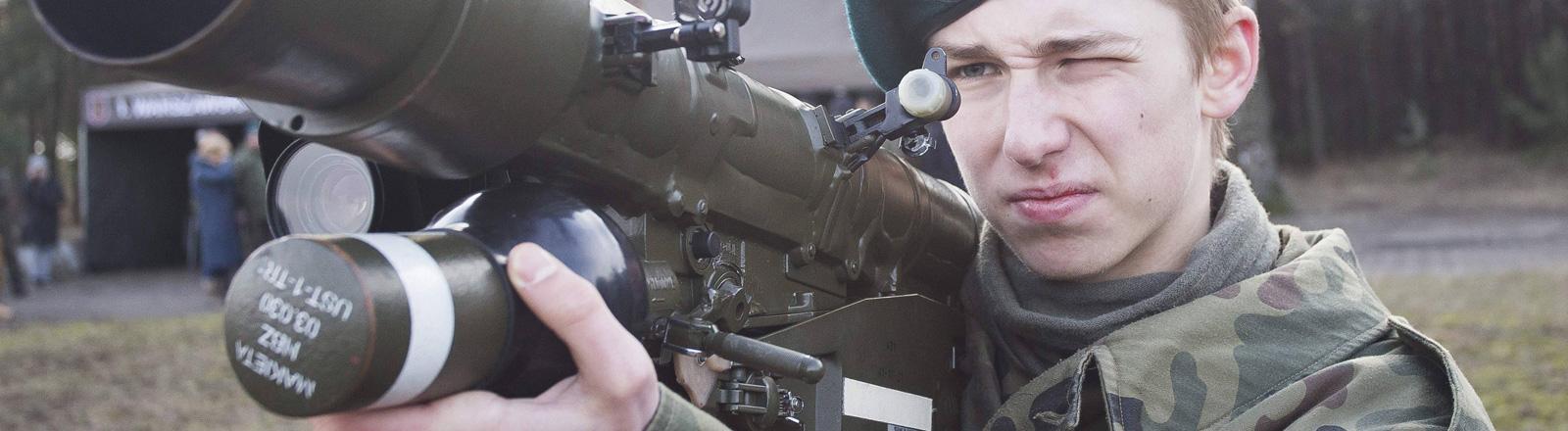 Ein junger Freiwilliger einer paramilitärischen Einheit in Polen hält einen Raketenwerfer in der Hand.