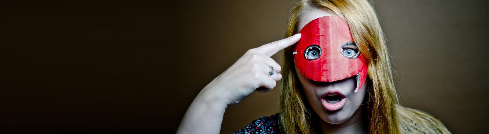 Eine Frau mit Sprechblasenmaske zeigt den Vogel.