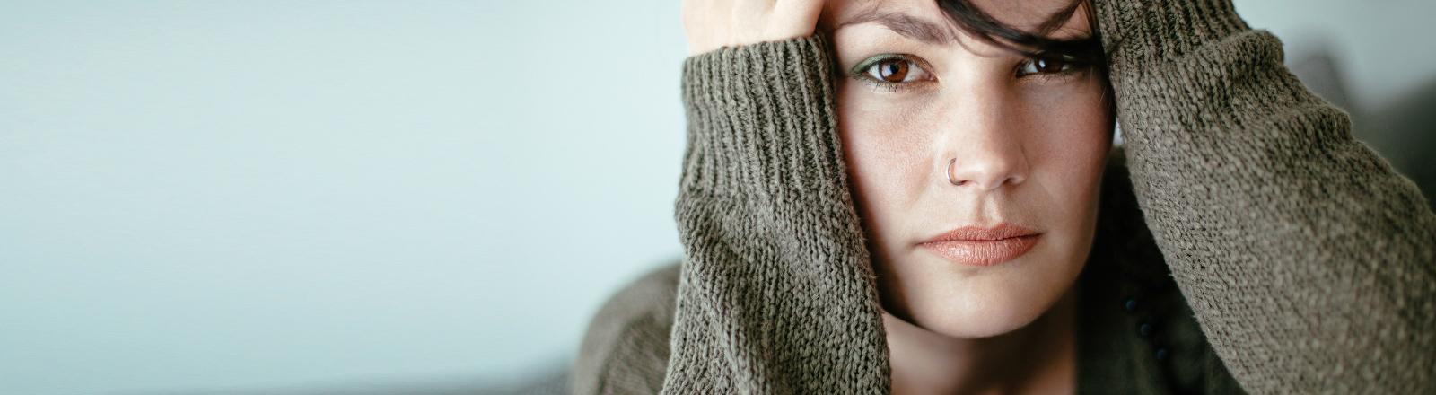 Eine Frau hält genervt ihren Kopf.