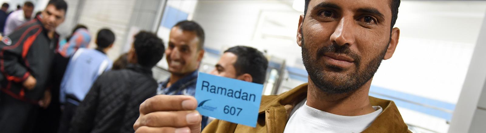 Der Asylbewerber Mohamed hält in der Erstaufnahmestelle für Flüchtlinge in Meßstetten eine blaue Essensmarke in der Hand auf der Ramadan steht. Es ist nach Sonnenuntergang; Foto: dpa