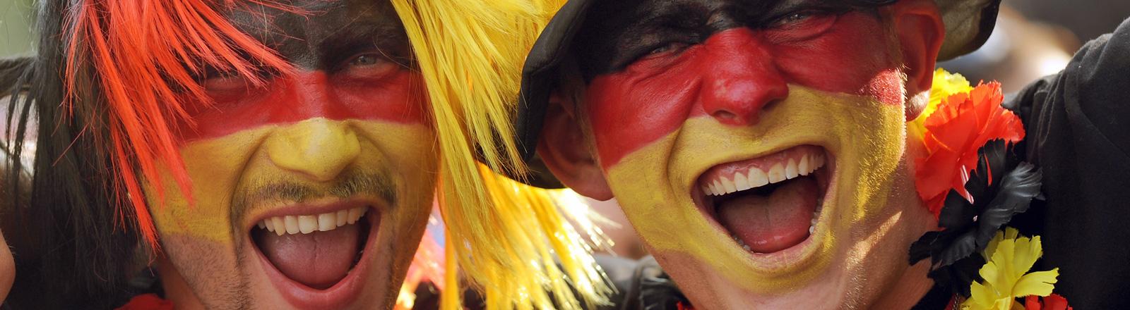 Zwei Fußballfans haben ihre Gesichter in den Deutschlandfarben geschminkt; Foto: dpa