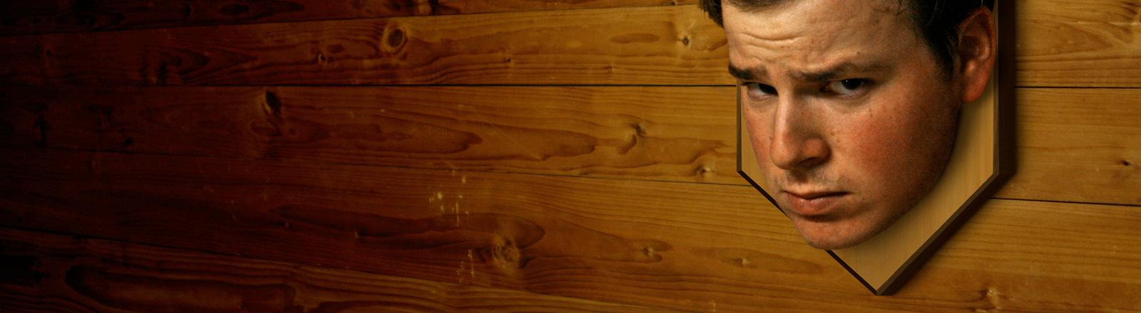 Der Kopf eines Mannes hängt wie eine Jagdtrophäe an einer Holzwand.