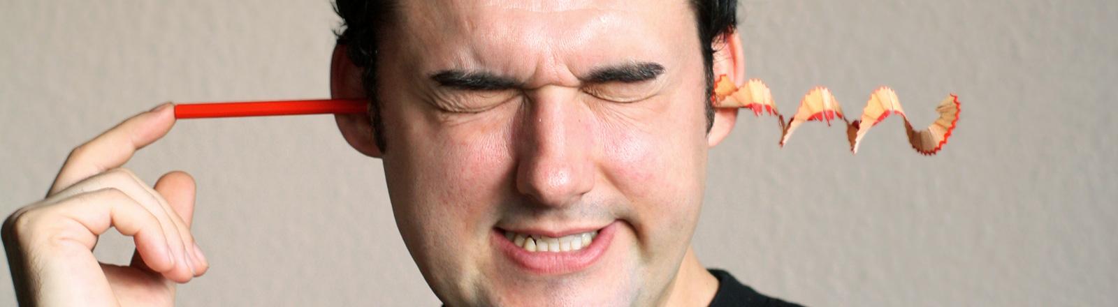 Ein Mann hält an das eine Ohr einen Bleistift. Aus dem anderen Ohr fällt Spitzabfall.