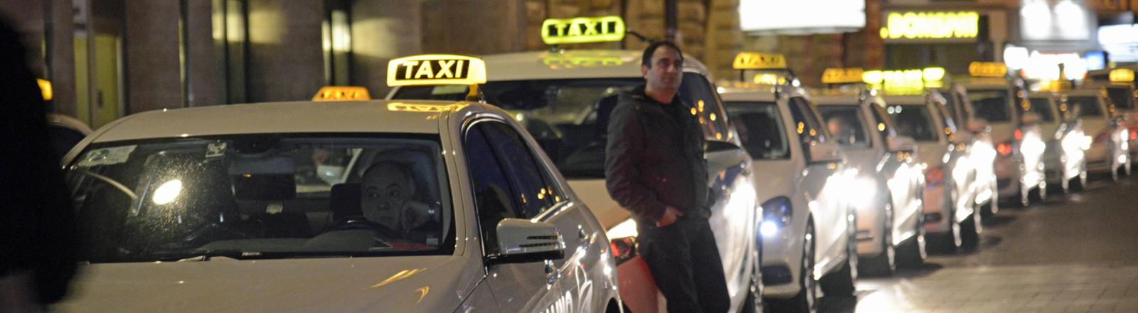 Eine Reihe von Taxis steht hintereinander.