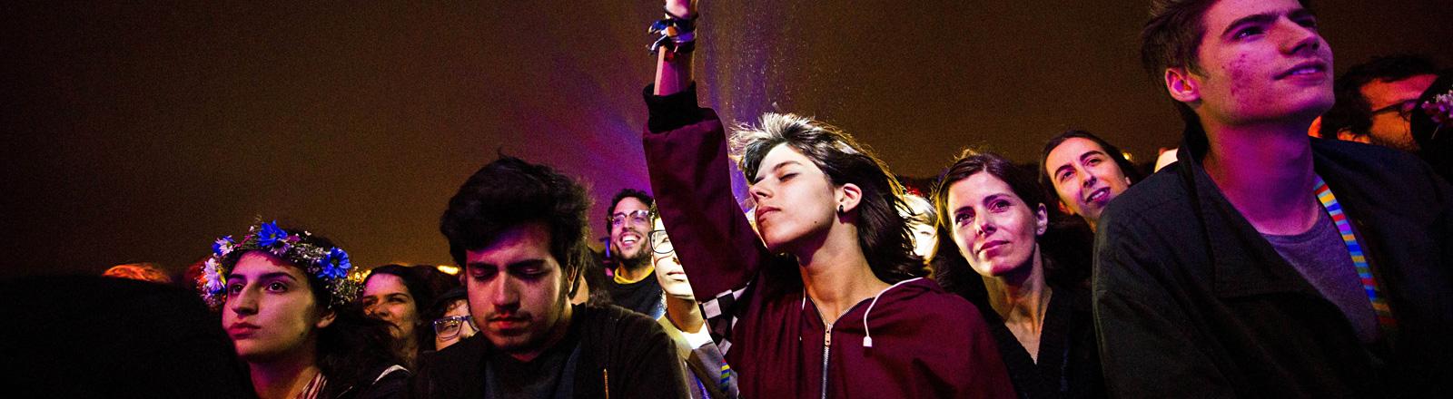 Auf dem Primavera Sound-Festival stehen Fans direkt vor der Bühne. Eine Frau reckt ihre rechte Hand in die Luft und hat die Augen geschlossen (6. Juni 2016).