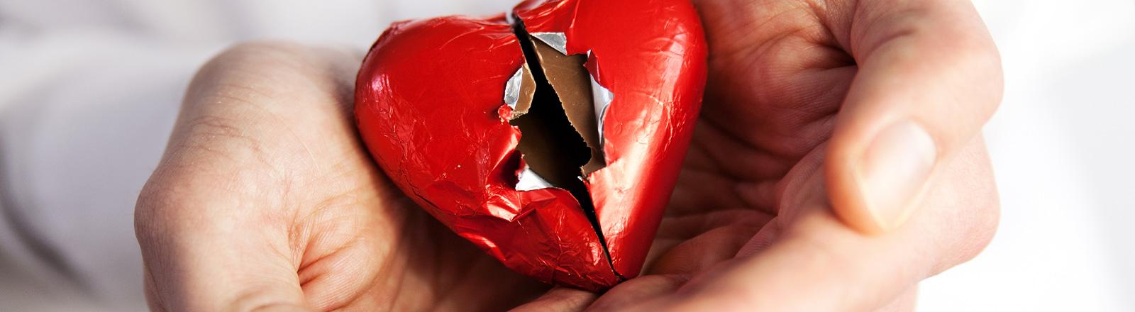 Zwei Hände halten ein Herz aus Schokolade mit roter Alu-Hülle. In der Mitte ist die Hülle kaputt.
