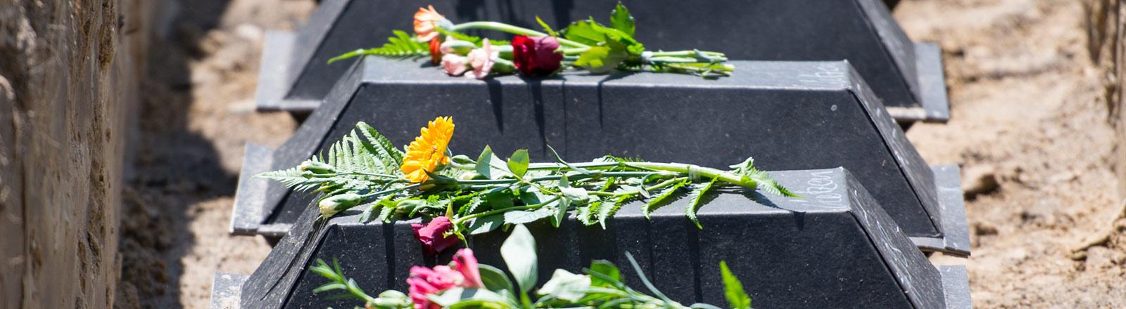 Aufgereihte Särge mit Blumen
