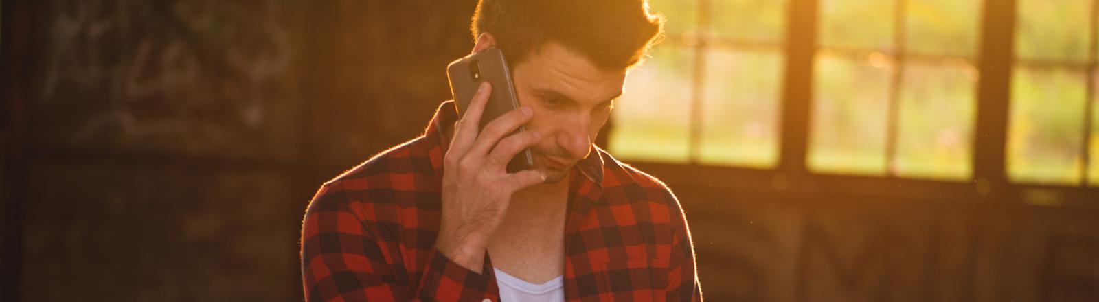 Ein Mann telefoniert mit seinem Mobiltelefon.