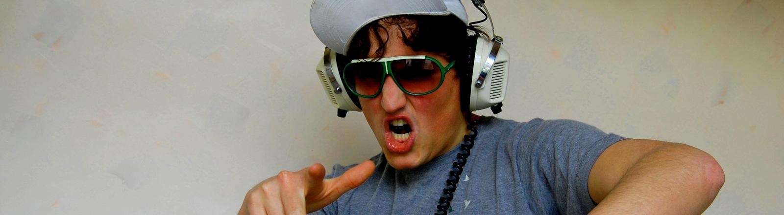 Ein Mann hat eine Kappe auf dem Kopf und Kopfhörer auf den Ohren. Er rappt mit den Armen.