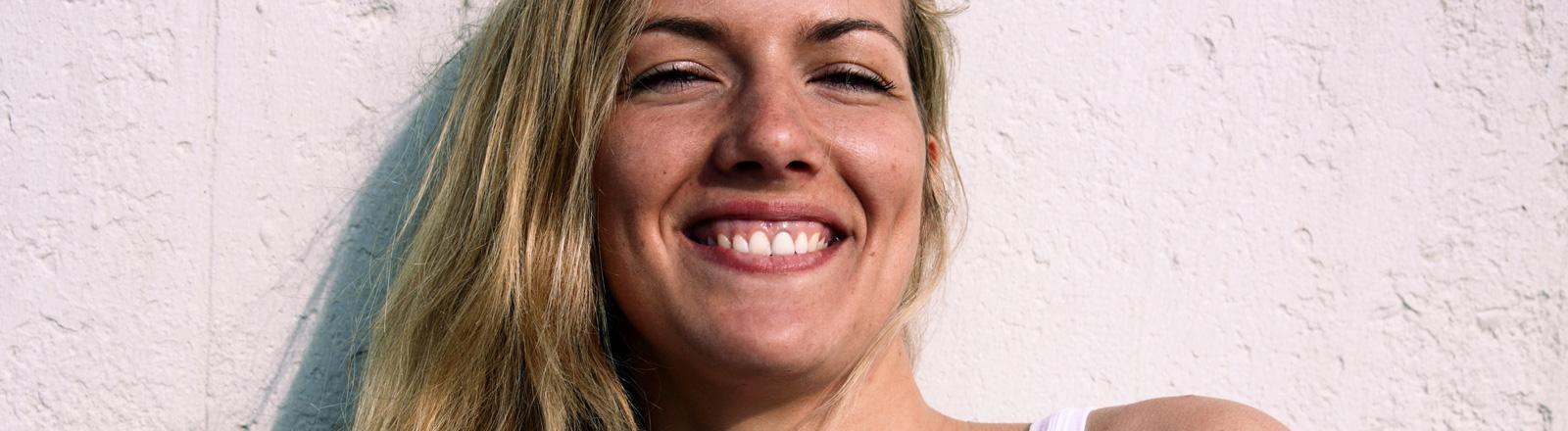 Eine Frau mit langen blonden Haaren lächelt.