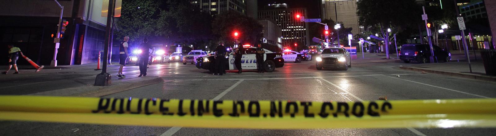 In der US-Stadt Dallas stehen Polizeiwagen auf einer Straßenkreuzung. Die Straße ist durch ein Band abgesperrt; Foto: dpa