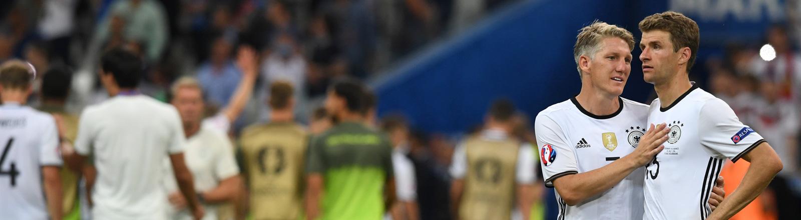 Nach dem Halbfinale Deutschland gegen Frankreich stehen Bastian Schweinsteiger und Thomas Müller nebeneinander auf dem Feld. Schweinsteiger scheint Müller zu trosten; Foto: dpa