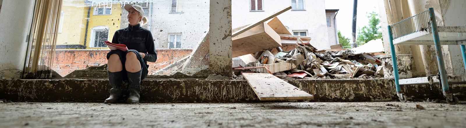 Eine Frau sitzt in einem zerstörten Haus in Simbach.