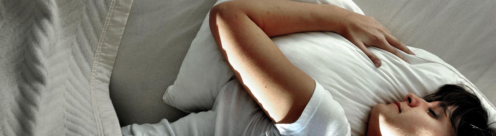 Frau schläft auf Matratze.