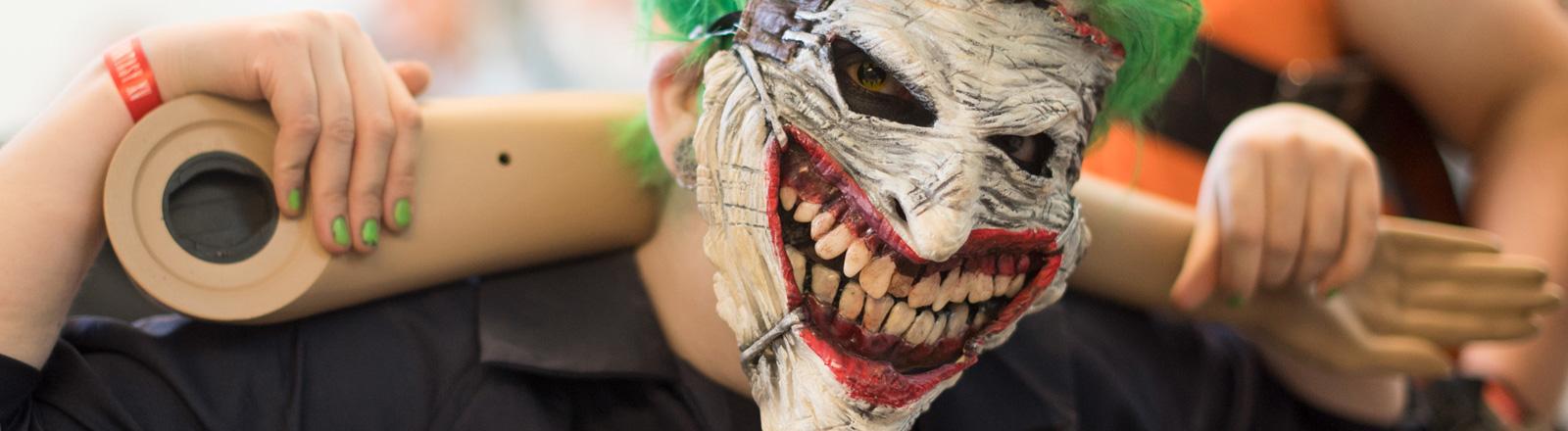 Auf der Spielemesse Gamescom 2016 hat sich eine Frau als Joker verkleidetet. Er hat grüne Haare und trägt eine Maske mit einem großen Mund und riesigen Zähnen; Foto: dpa