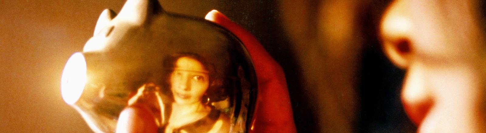 Eine Frau hält ein goldenes Sparschwein in der Hand. Ihr Gesicht spiegelt sich darin.