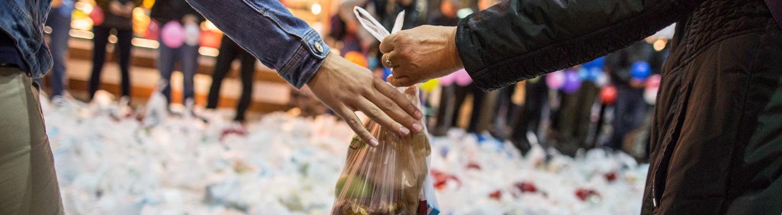 Freiwillige Helfer geben sich am 05.09.2015 in Frankfurt am Main im Hauptbahnhof selbst gepackte Tüten mit Lebensmitteln und Getränken weiter; Foto: dpa