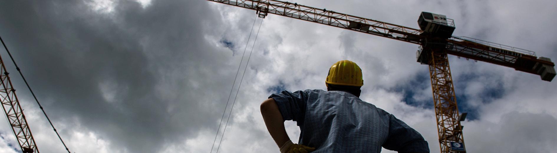 Ein Mann blickt auf einer Baustelle auf zwei Kräne; Foto: dpa
