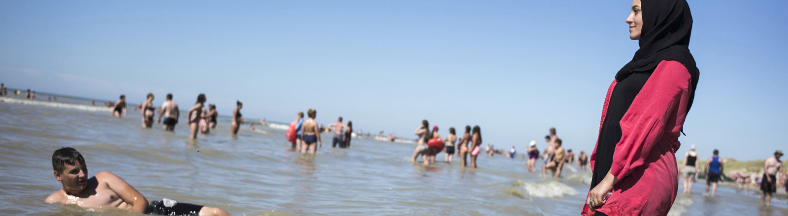 Am Meer steht eine Frau im Burkini. Im Wasser schwimmt ein Junge; Foto: dpa