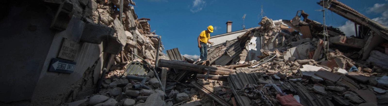 Das italienische Dorf Amatrice wurde durch ein Erdbeben (24.08.16) stark zerstört. Ein Mann mit gelbem Schutzhelm steht auf einem riesigen Schutthaufen aus Häusern.