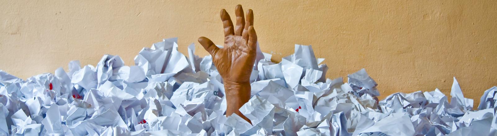 Aus einem Papierberg reckt eine künstliche Hand heraus.