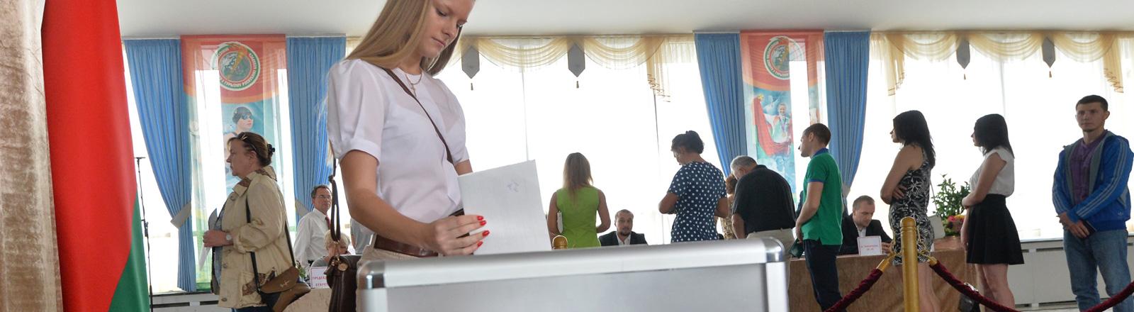 In einem Wahllokal in Minsk (11.09.2016) wirft eine junge Frau ihren Stimmzettel in eine große graue Box. Hinter ihr stehen weitere Wähler an einem Tisch an; Foto: dpa