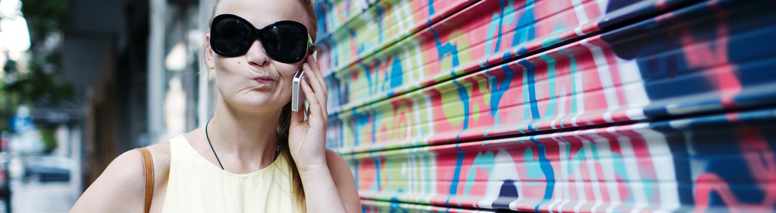 Eine Frau steht auf einer Straße. Sie trägt ein gelbes Kleid und eine schwarze Sonnenbrille. Mit ihrer linken Hand hält sie ein Mobiltelefon ans Ohr. Sie verzieht ihren Mund und wirkt dadurch leicht genervt.