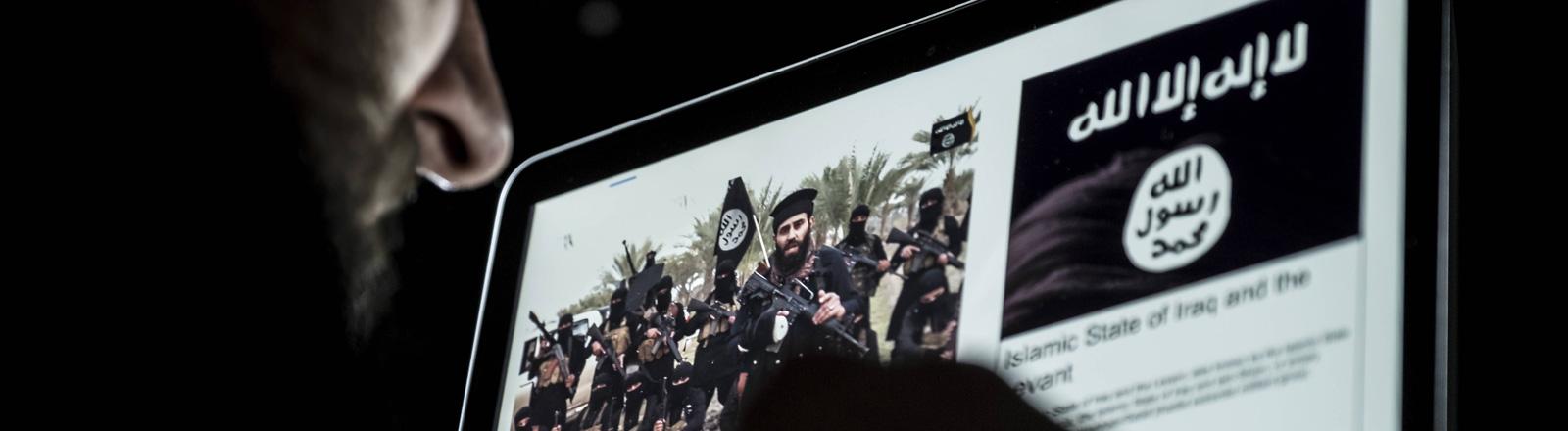 Ein Mann schaut sich ein Video des IS auf dem Laptop an.