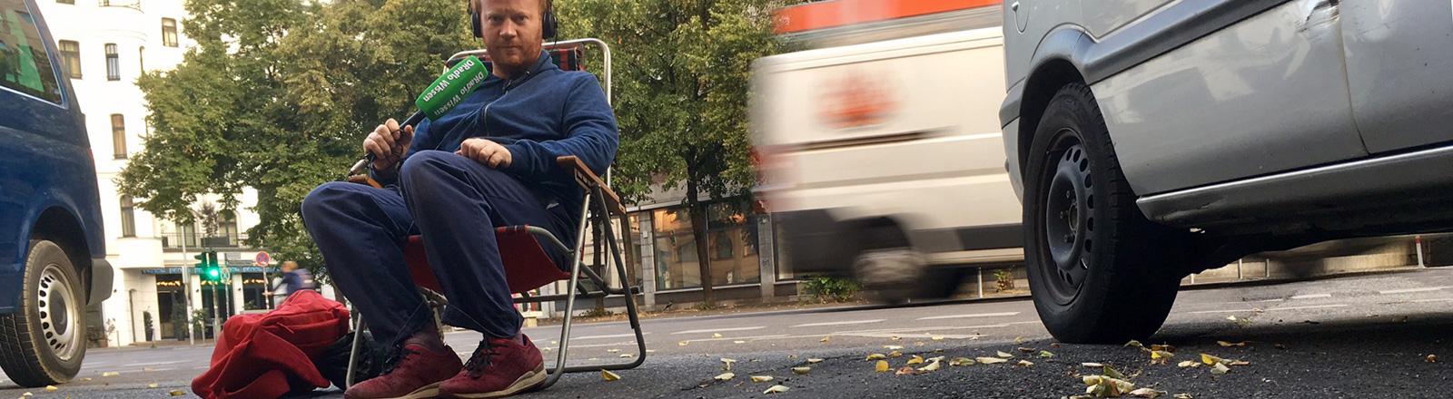 Reporter Moritz Metz sitzt auf einem Liegestuhl auf einem Parkplatz mitten in Berlin.