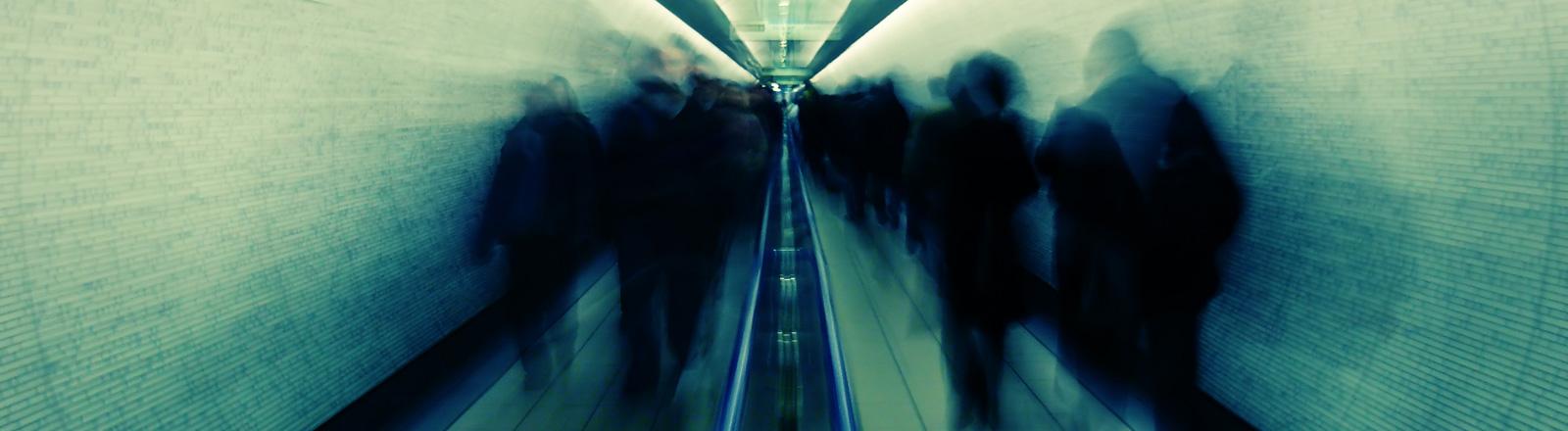 Durch einen Tunnel laufen Menschen, die nur schattenhaft zu erkennen sind.
