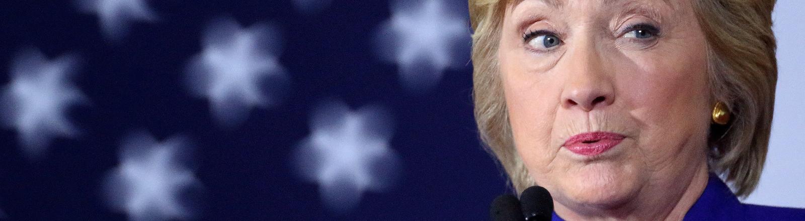 Hillary Clinton vor der US-Flagge.