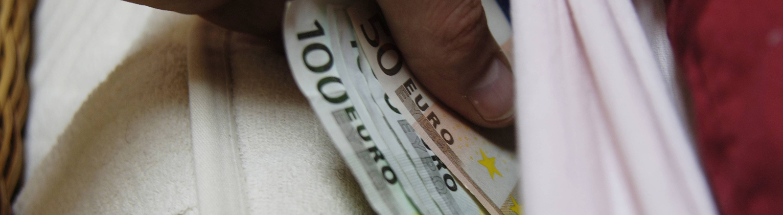 Geld in die Matratze schieben