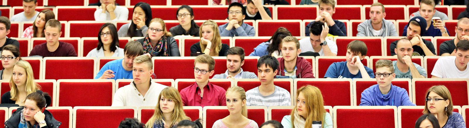 Studenten sitzen in verschiedenen Reihen in einem Hörsaal