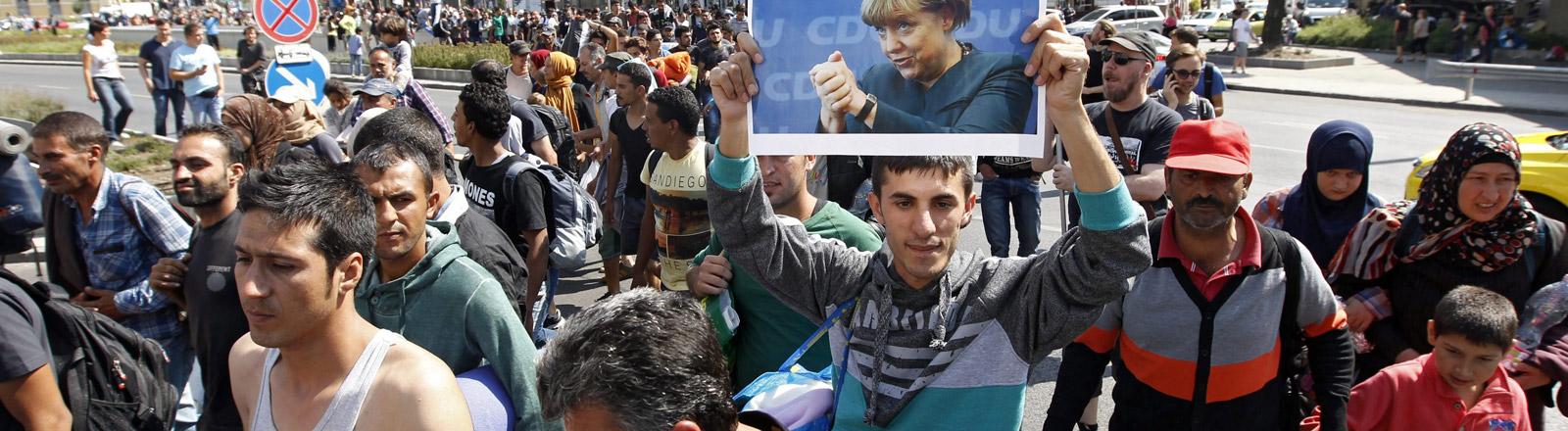 Flüchtlinge auf ihrem Weg. Ein Mann hält ein Plakat hoch, das Angela Merkel zeigt.