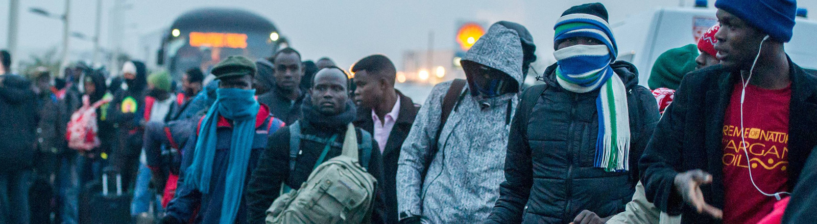 Flüchtlinge in Calais stehen in einer langen Schlange. Im Hintergrund steht ein Bus.