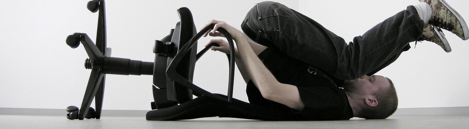 Auf dem Fußboden liegt ein Bürostuhl mit Rollen und ein Mann auf dem Rücken. Er scheint vom Stuhl gerutscht zu sein und hält sich an den Lehnen fest.