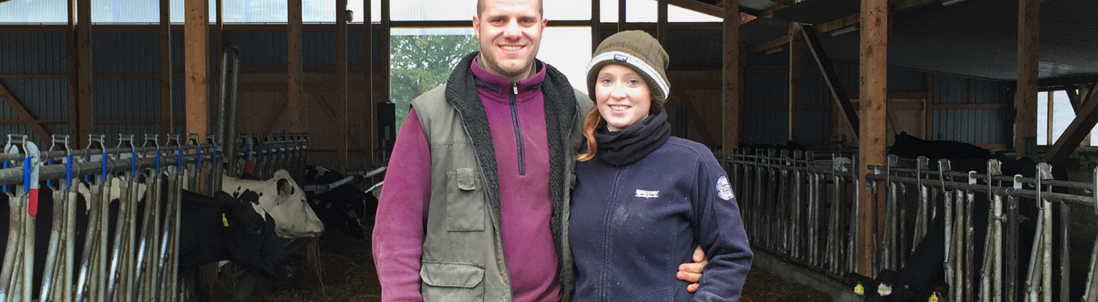 Cathrin und Sven Rosenau-Gewe stehen nebeneinander auf ihrem Hof. Im Hintergrund blickt man in einen großen Stall mit Kühen.
