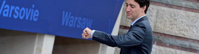 Kanadas Premierminister Justin Trudeau bei einem Besuch in Warschau. Er geht über einen Platz und blickt auf seine Uhr am linken Handgelenk; Foto: dpa