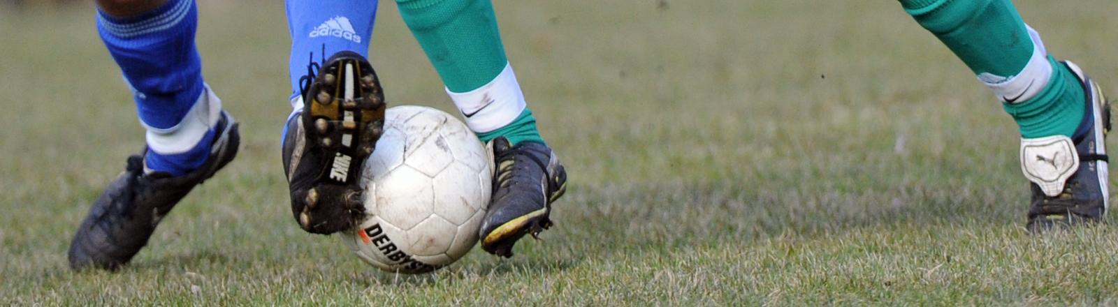 Fußballer treten gegen einen Ball.