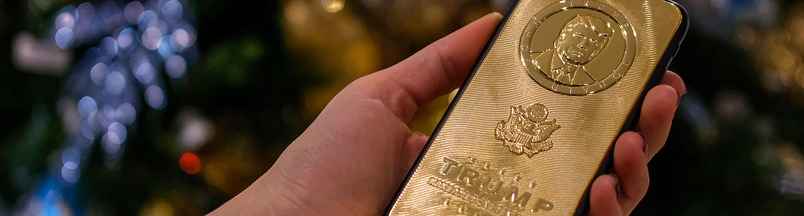 Goldenes Handy mit Trump-Schriftzug und Portrait