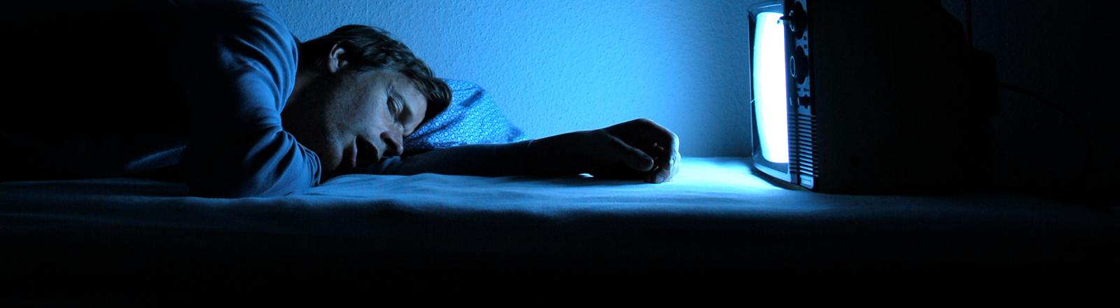 Ein Mann ist vor dem Fernseher eingeschlafen.