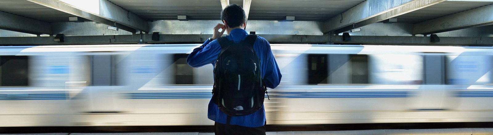 Ein Mann steht vor einer vorbeirauschender Bahn in San Francisco.