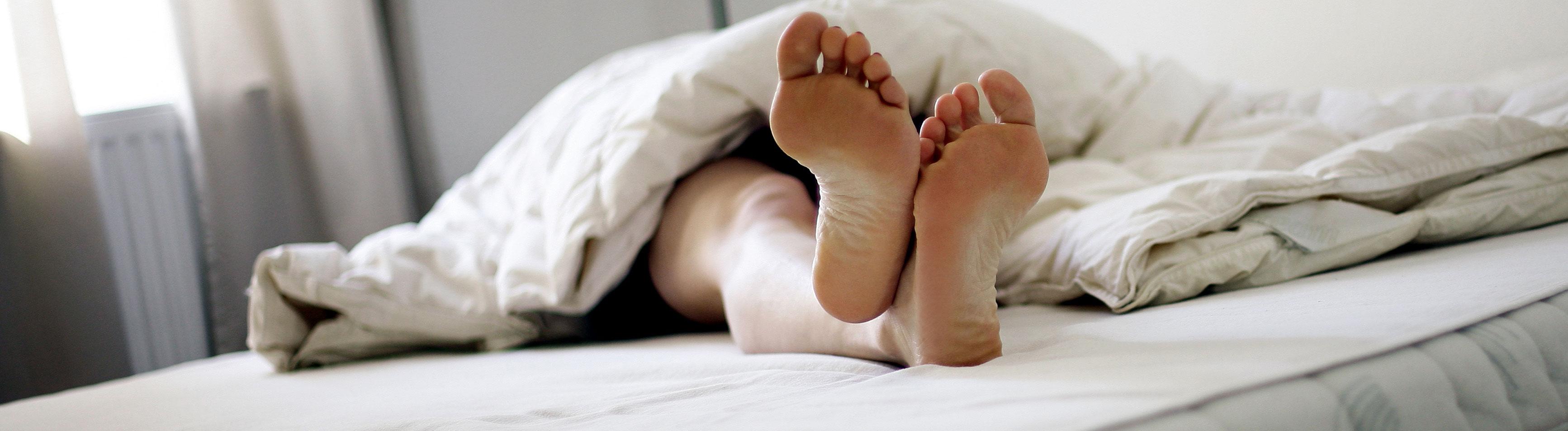 Eine Person liegt auf einer Matratze. Die Füße lugen unter der Bettdecke hervor.