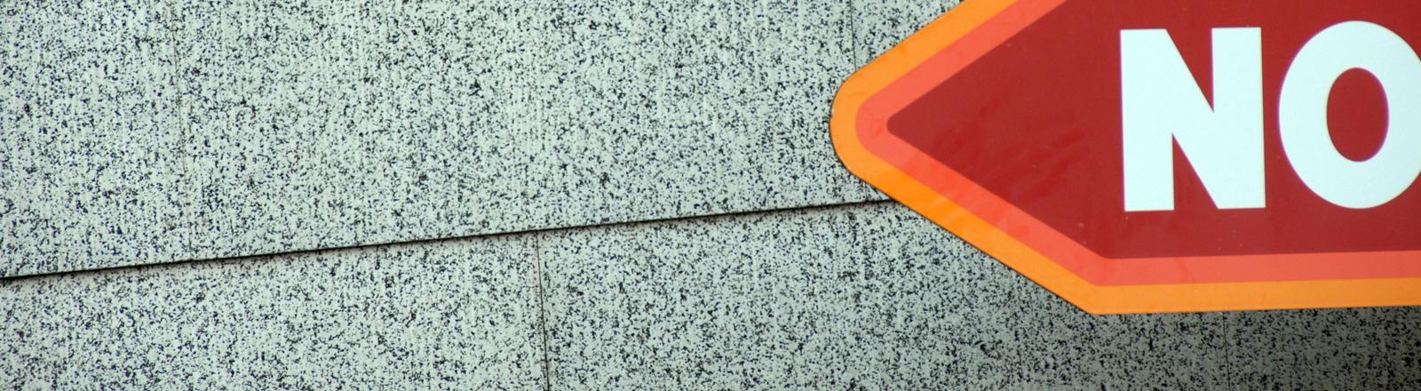 """Ein rot-orangenes Schild lugt von rechts in das Bild hinein. Die Buchstaben """"NO"""" stehen darauf, der Rest ist abgeschnitten."""