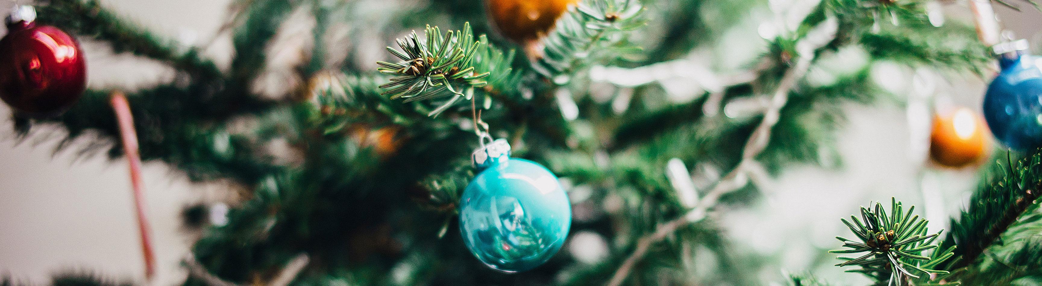 An einem Weihnachtsbaum hängen Kugeln.