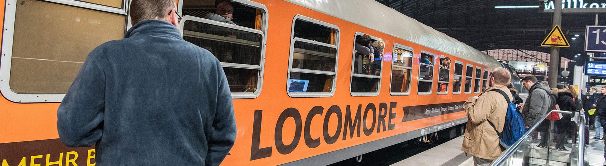 Ein orangefarbener Zug steht im Bahnhof. Aus einzelnen Fenster schauen Fahrgäste raus. Auf dem Zug steht Locomore; Foto: Bild York Christoph Riccius