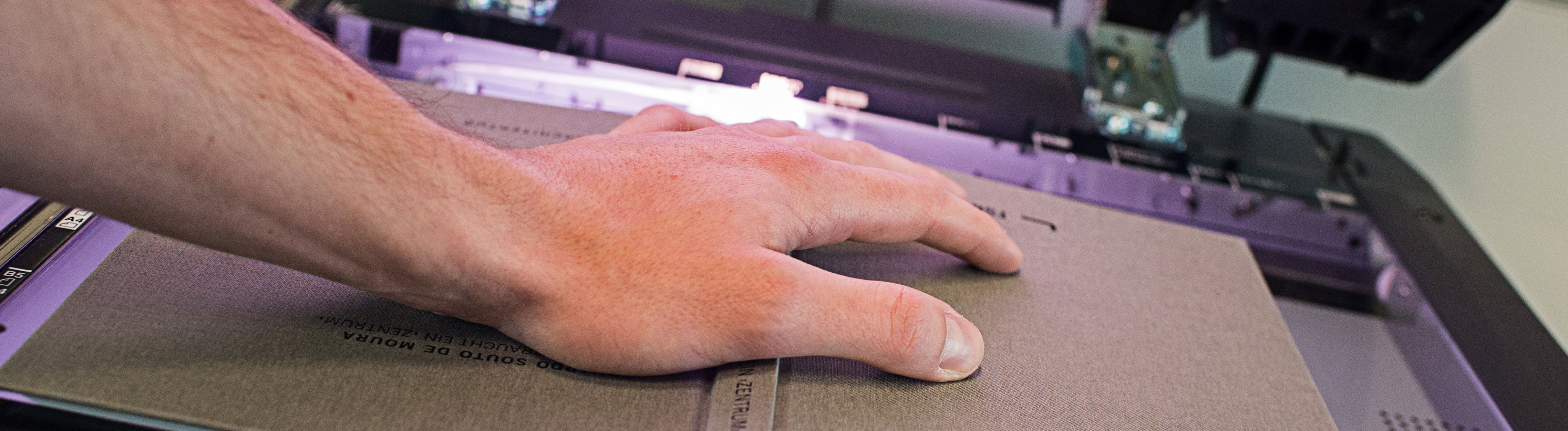 Ein Buch liegt aufgeschlagen auf einem Kopiergerät. Ein Hand liegt auf dem Buch; Foto: dpa